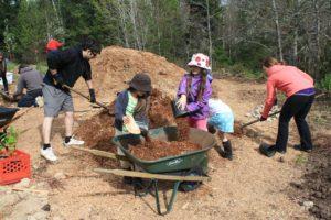 Children load a wheelbarrow with bark mulch